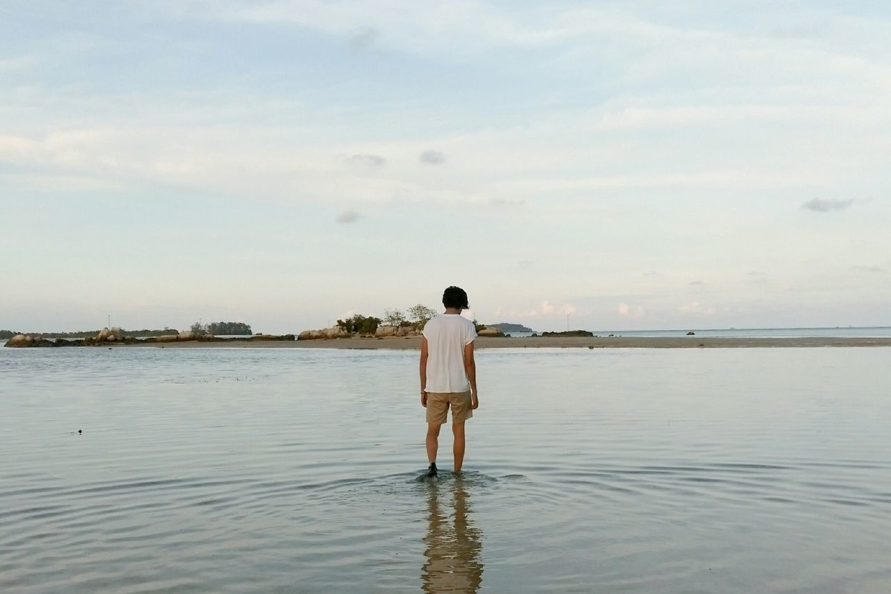 Rear view of man standing with ankle deep in sea against sky