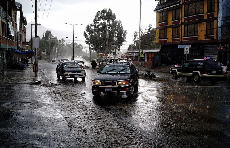 Cars parked on wet street during rainy season
