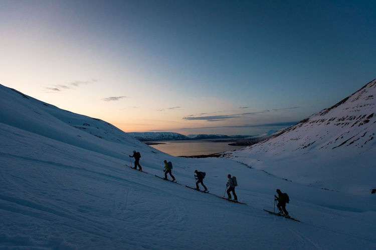 People on snow covered mountain against sky during sunset