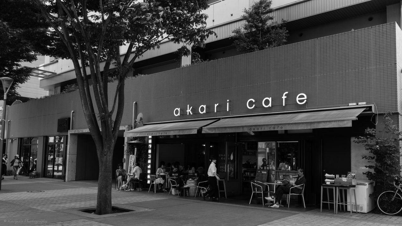 western script, text, building exterior, communication, architecture, food and drink industry, restaurant, built structure, cafe, outdoors, awning, sidewalk cafe, day, store, tree, no people, city