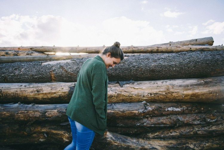 Woman standing near logs
