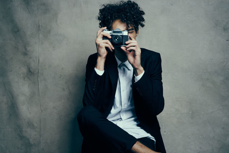 Full length of young man photographing against wall