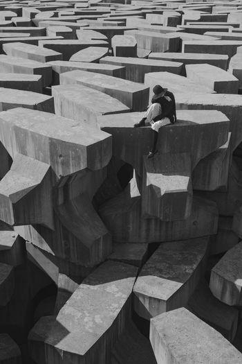 High Angle View Of Woman Sitting On Rocks