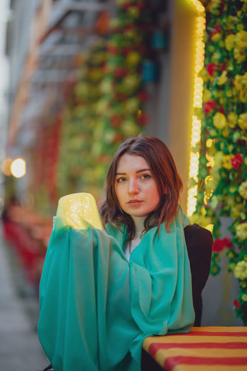 Portrait of beautiful woman holding illuminated jar and scarf while sitting in city at dusk