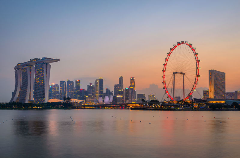 Illuminated Singapore Flyer And Buildings By Sea In City At Sunset
