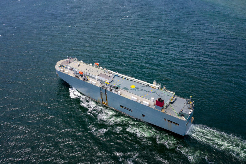 Aerial view of large roro vehicle carrier vessel sailing on the green sea