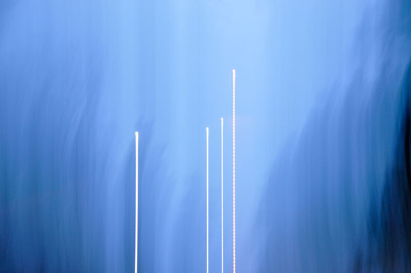 Low angle view of illuminated vapor trail against blue sky