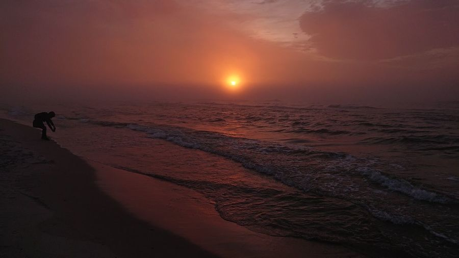 Sunset by the see Sea Sunset Beach Silhouette Sand Water Sun Atmospheric Mood Romantic Sky Moody Sky Atmosphere