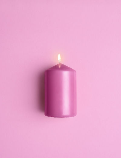 Close-up of lit candle against pink background