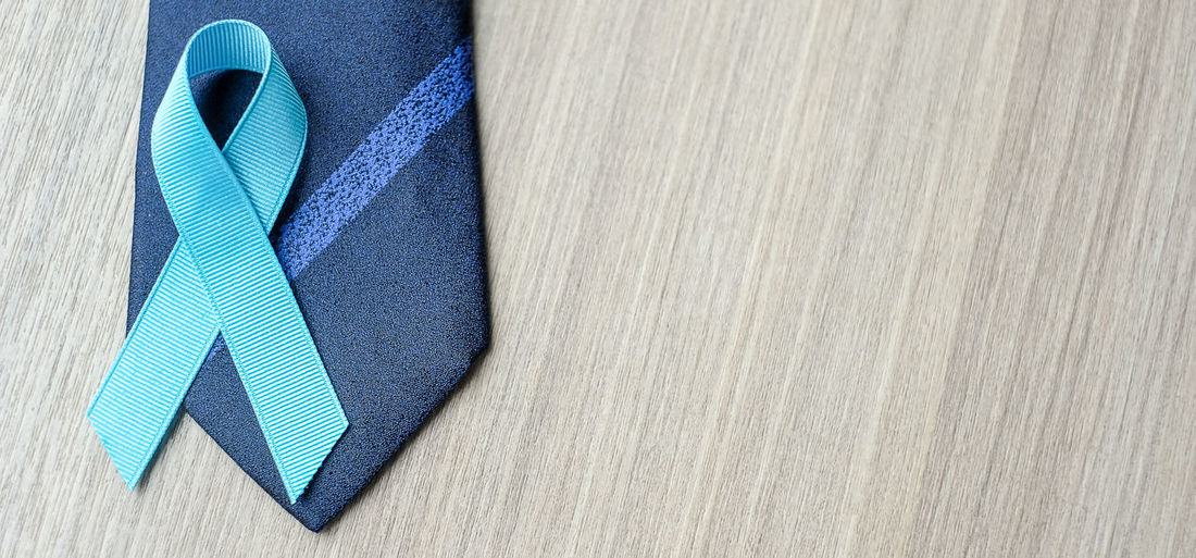 Directly above view of blue ribbon on necktie over table