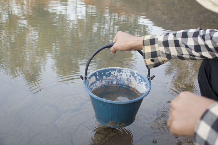 Midsection of person holding water bucket
