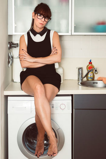 Full length of woman sitting on washing machine