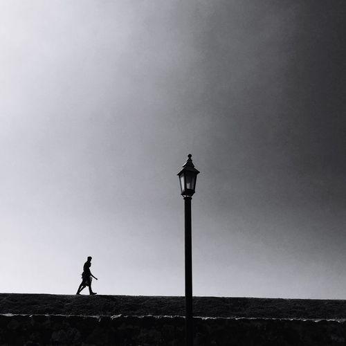 Silhouette woman walking on field by street light against sky