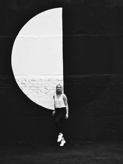 Portrait of woman levitating against wall
