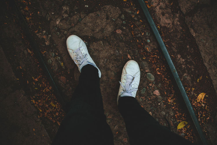 Autumn colors Fashion Stories Train Tracks Black Pants Canvas Shoe Contrast Day Directly Above Fashion Photography High Angle View Human Body Part Human Leg Leafs On The Ground Low Section Men One Person Outdoors People Personal Perspective Real People Shoe Shoes Standing Whiteshoes