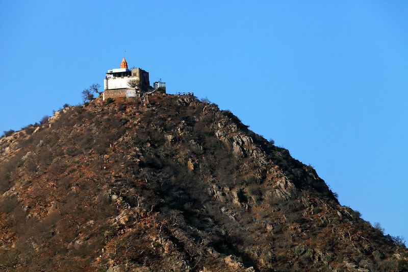 Low angle view of historic building on mountain against clear blue sky