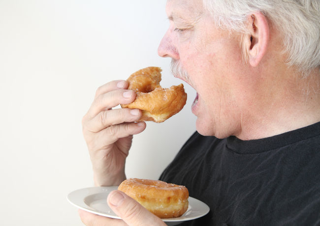 Older man eats glazed doughnut Breakfast Copy Space Doughnuts Fatty Foods Fingers Food Hands Junk Food Man Mouth Open Older Person Profile Senior Snack Sugary Sweet Food Treats Unhealthy Eating