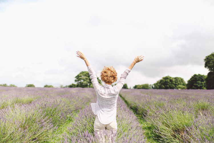 Rear view of woman with arms outstretched on lavender field against sky