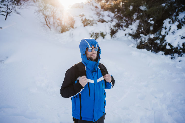 Man standing on snow covered land during winter