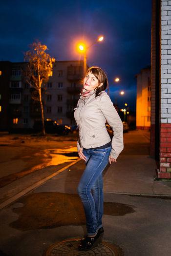 Woman standing on illuminated street at night