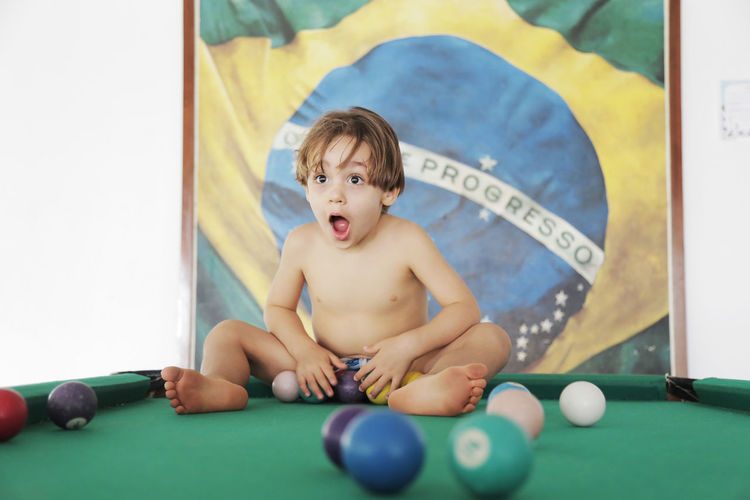 Boy Playing With Balls On Pool Table