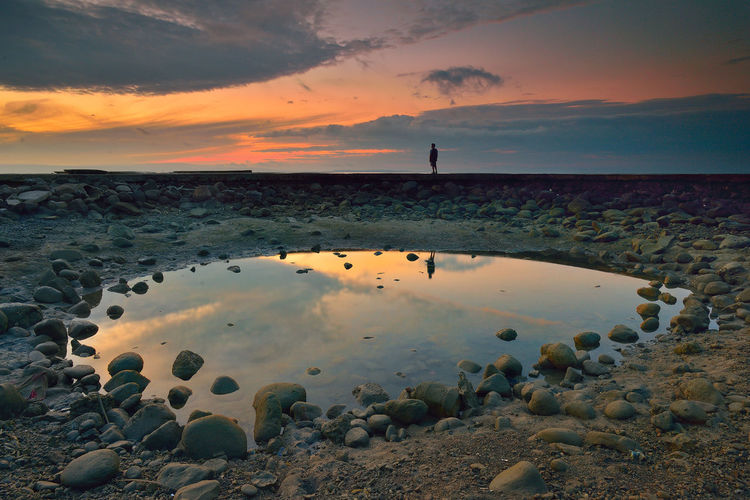 Puddle On Beach Against Cloudy Sky At Sunset