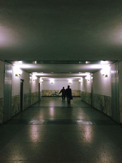Rear view of people walking in subway