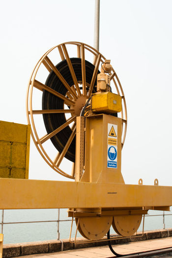 Low angle view of yellow wheel against clear sky