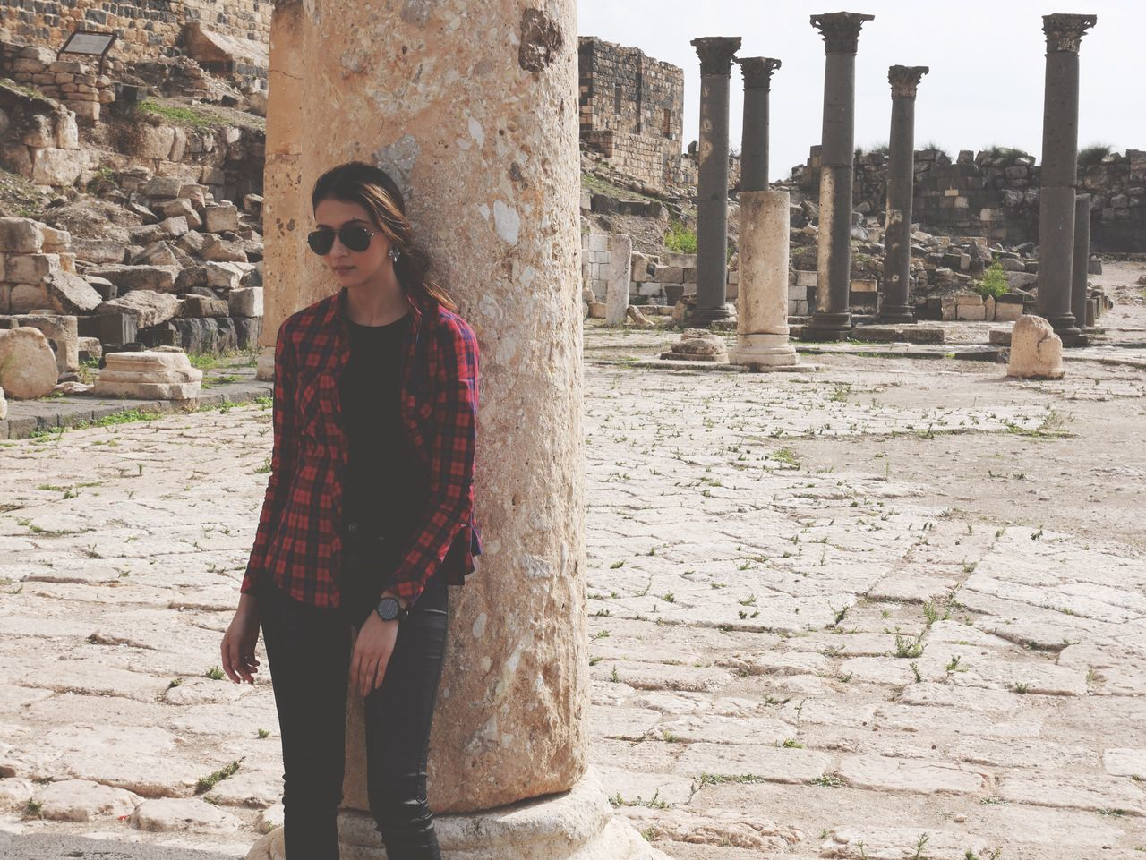Young Woman Leaning On Column At Old Historic Ruins