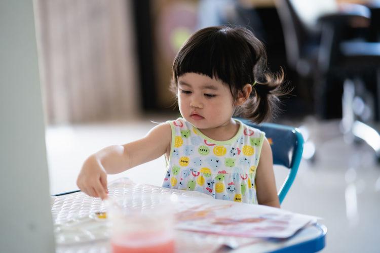 Portrait of cute girl preparing food on table