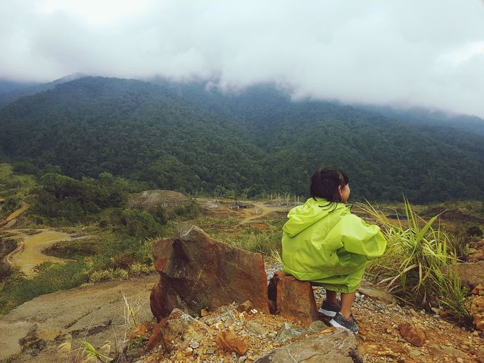 Girl Sitting On Rock By Landscape And Mountains Against Cloudy Sky