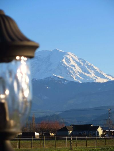 Close-up of lamp with snowcapped mt rainier in background against clear sky