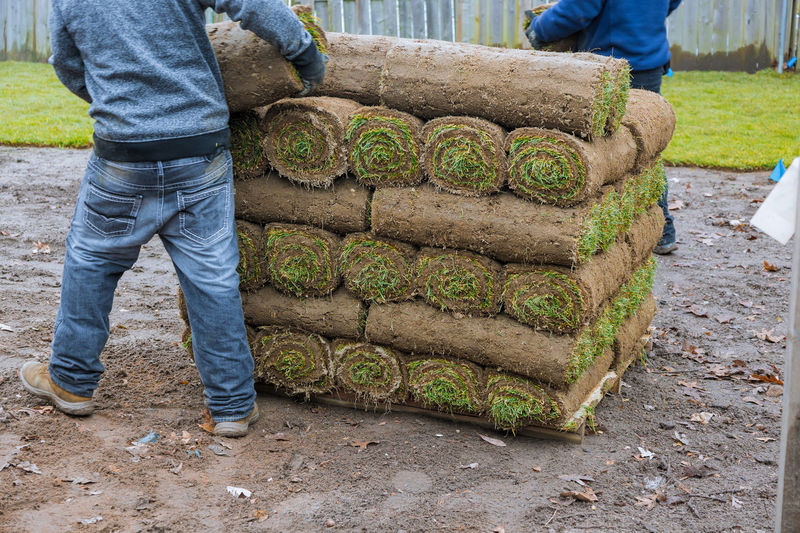 Low section of man stacking turf outdoors