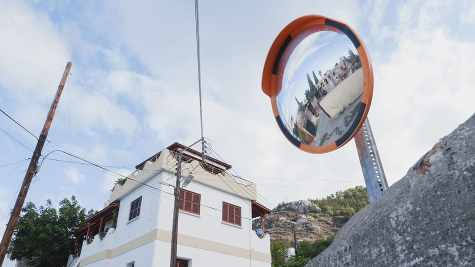 A convex road mirror in narrow roads near a town in Nicosia, North Cyprus. Mirror Architecture Building Exterior Built Structure Cable Cloud - Sky Communication Convex Mirror Convex Mirrors Day Low Angle View No People Outdoors Road Mirror Sky Tree