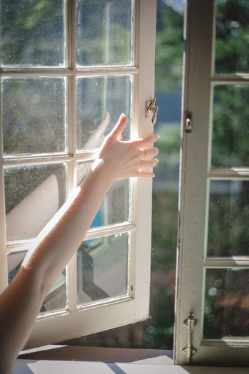 Cropped Hand Of Woman Opening Window