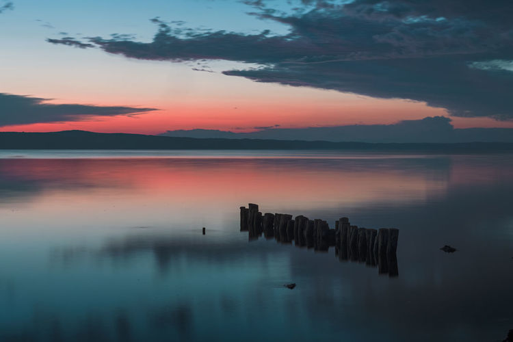Calmness Calmness Within Quiet Moments Scenic Beauty In Nature Cloud - Sky Lake Landscape Long Exposure Moody Nature No People Outdoors Pillars Reflection Been There. Rewilding Scenics Silhouette Sky Sunset Tranquil Scene Tranquility Water Waterfront