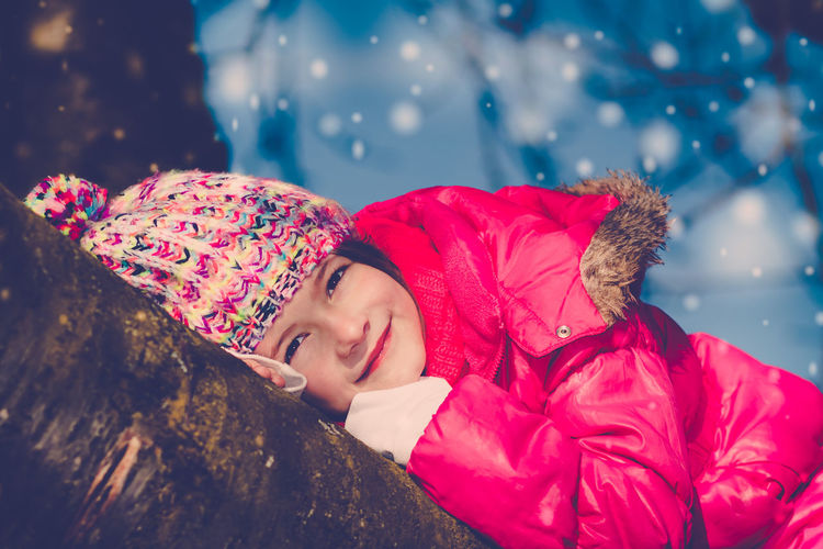 Young girl smiling at camera lying on a tree trunk enjoying magical winter light Happy Tree Trunk Winter Winter Clothes Winter Sky Wintertime Age 6-9 Blue Bobble Hat  Close-up Magical Winter Sky Nature One Person Outdoors Portrait Real People Red Smiling Snowflake Snowing Tree Warm Clothing Wearing Winter Wonderland Young Girl