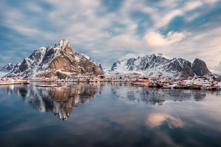 Mountain range reflection on arctic ocean with scandinavian village on winter at Lofoten Islands, Norway Water Cloud - Sky Sky Mountain Reflection Scenics - Nature Beauty In Nature Tranquil Scene Cold Temperature Mountain Range Waterfront Tranquility Winter Nature Snow Lake No People Idyllic Snowcapped Mountain