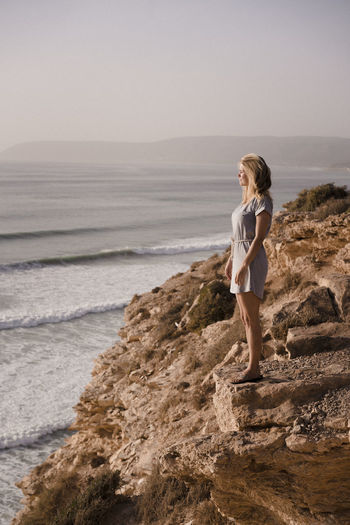 Girl spotting waves from a cliff Marocco Landscape Africa North Africa Cliff Girl Standing Surface Level Waves Ocean Atlantic Surfing Surfcamp Spot Morocco Morocco Landscape