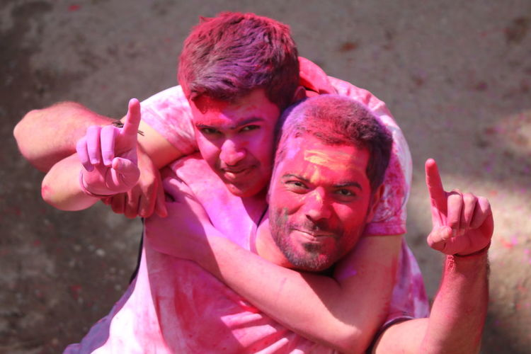 Portrait Of Smiling Friends Gesturing During Holi