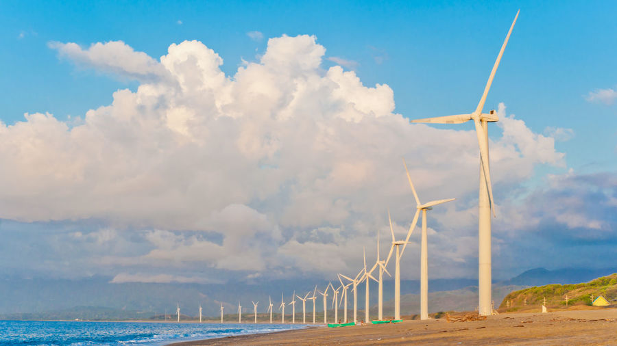 Wind turbines on beach against cloudy sky