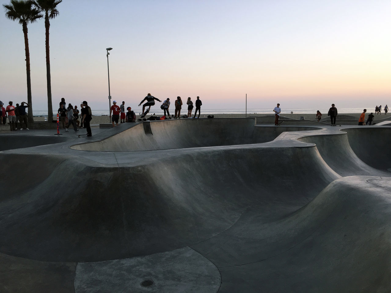 sunset, large group of people, real people, leisure activity, lifestyles, sport, weekend activities, water, skateboard park, travel destinations, vacations, enjoyment, nature, beach, men, outdoors, sky, sea, clear sky, beauty in nature, day, people