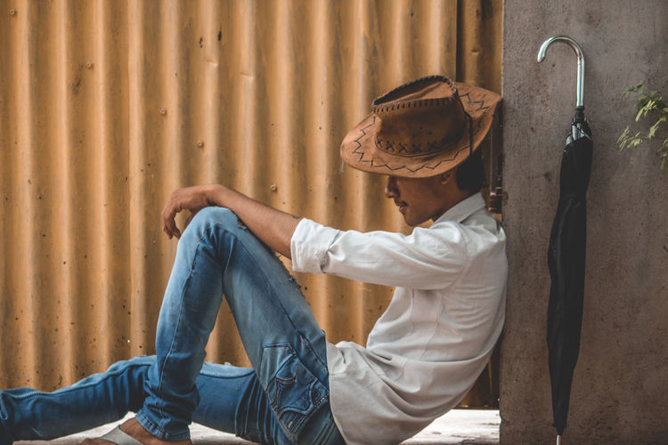 Teenage boy wearing hat sitting against corrugated iron