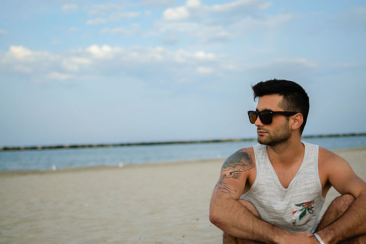 Young Man Wearing Sunglasses At Beach Against Sky