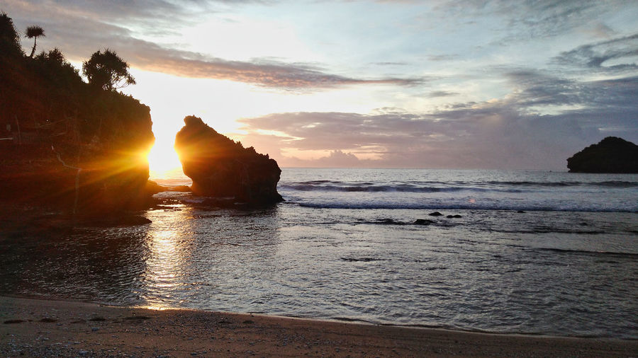 Srau Beach, Pacitan, Jawa Timur, Indonesia. Sea Sky Water Beach Sunset Beauty In Nature Land Scenics - Nature Cloud - Sky Nature Tranquility Rock Tranquil Scene No People Rock - Object Horizon Over Water Idyllic Wave Solid Sun Outdoors Lens Flare Stack Rock Nature Beauty In Nature