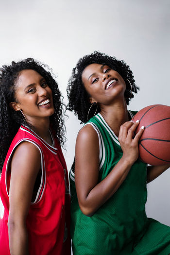Two black women wearing basketball jerseys holding basketball on a white background