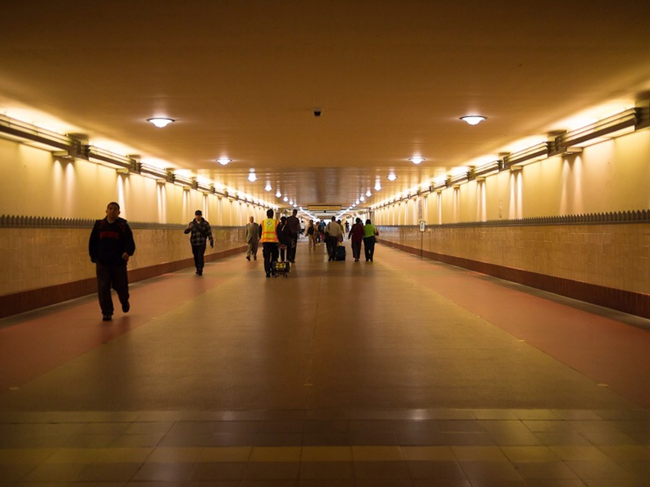 indoors, illuminated, men, ceiling, subway station, lifestyles, transportation, railroad station, subway, walking, airport, person, flooring, railroad station platform, large group of people, architecture, lighting equipment, built structure, public transportation