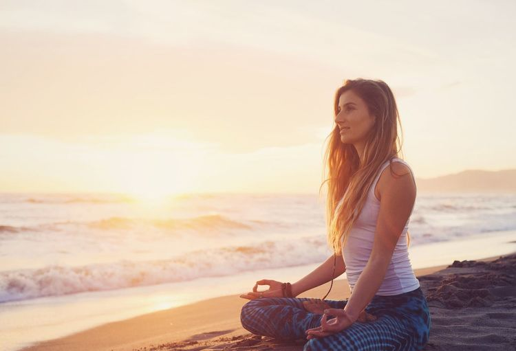 Young woman sitting on beach against sky during sunset
