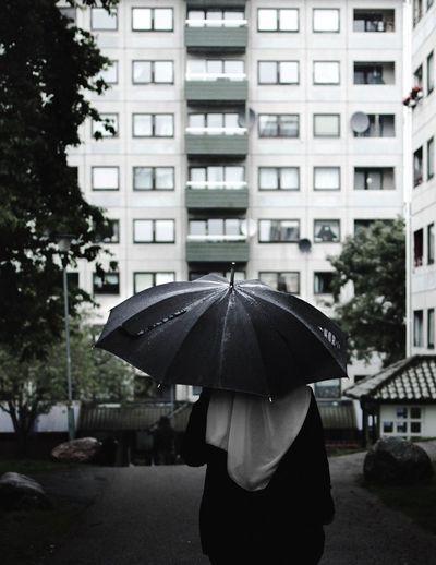 Rear view of woman walking in rain