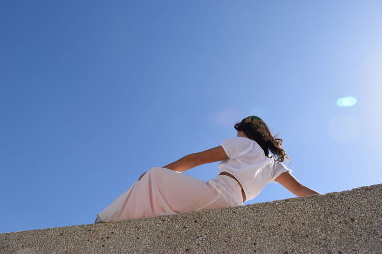 Low angle view of person against clear sky
